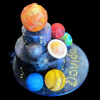 Torta decorata con ganache al fondente e pianete in pasta di zucchero per un compleanno