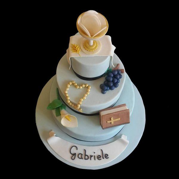 Torta decorata in pasta di zucchero con elementi sacri cristiani per una Comunione