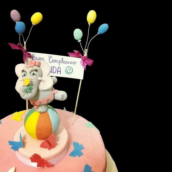 Torta decorata in pasta di zucchero con un elefantino equilibrista per un compleanno