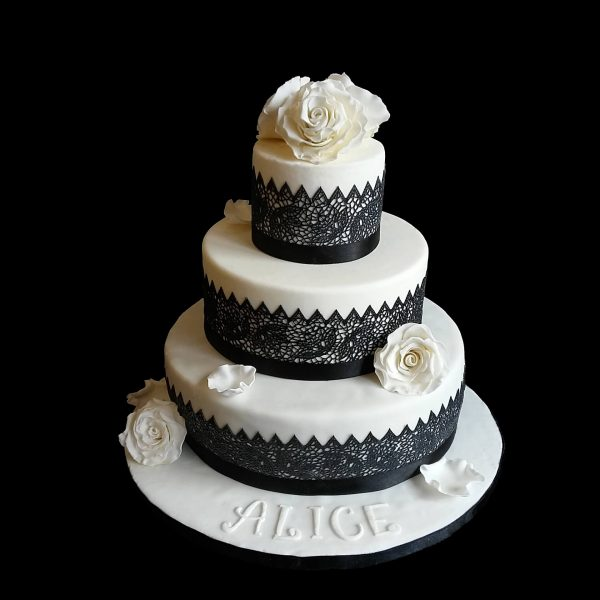 Torta decorata con rose bianche in pasta di zucchero e pizzi neri per una Cresima