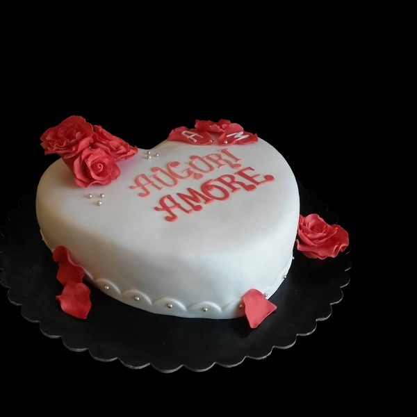 Torta a forma di cuore decorata con rose rosse in pasta di zucchero per un compleanno